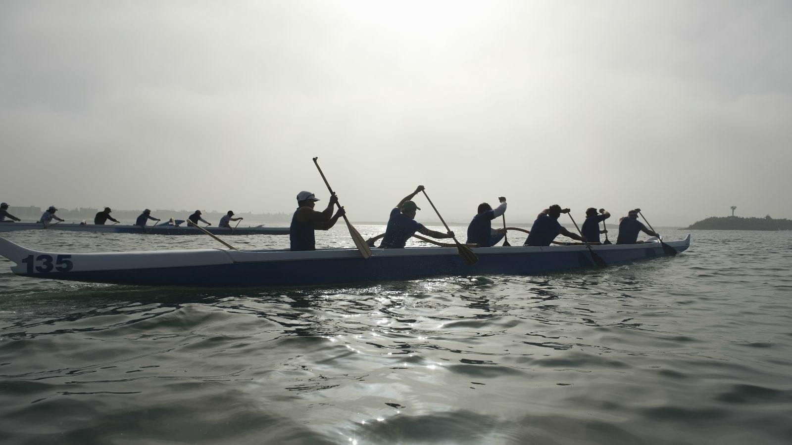 Boote mit aktiven Ruderern auf Wasser