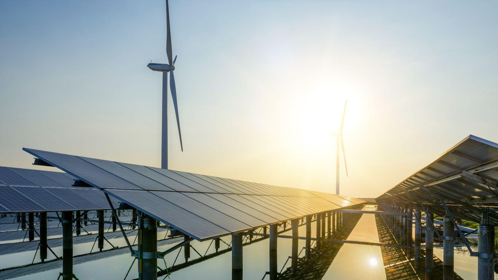 Photo mehrer Photovoltaikanlagen vor Windenergieanlagen