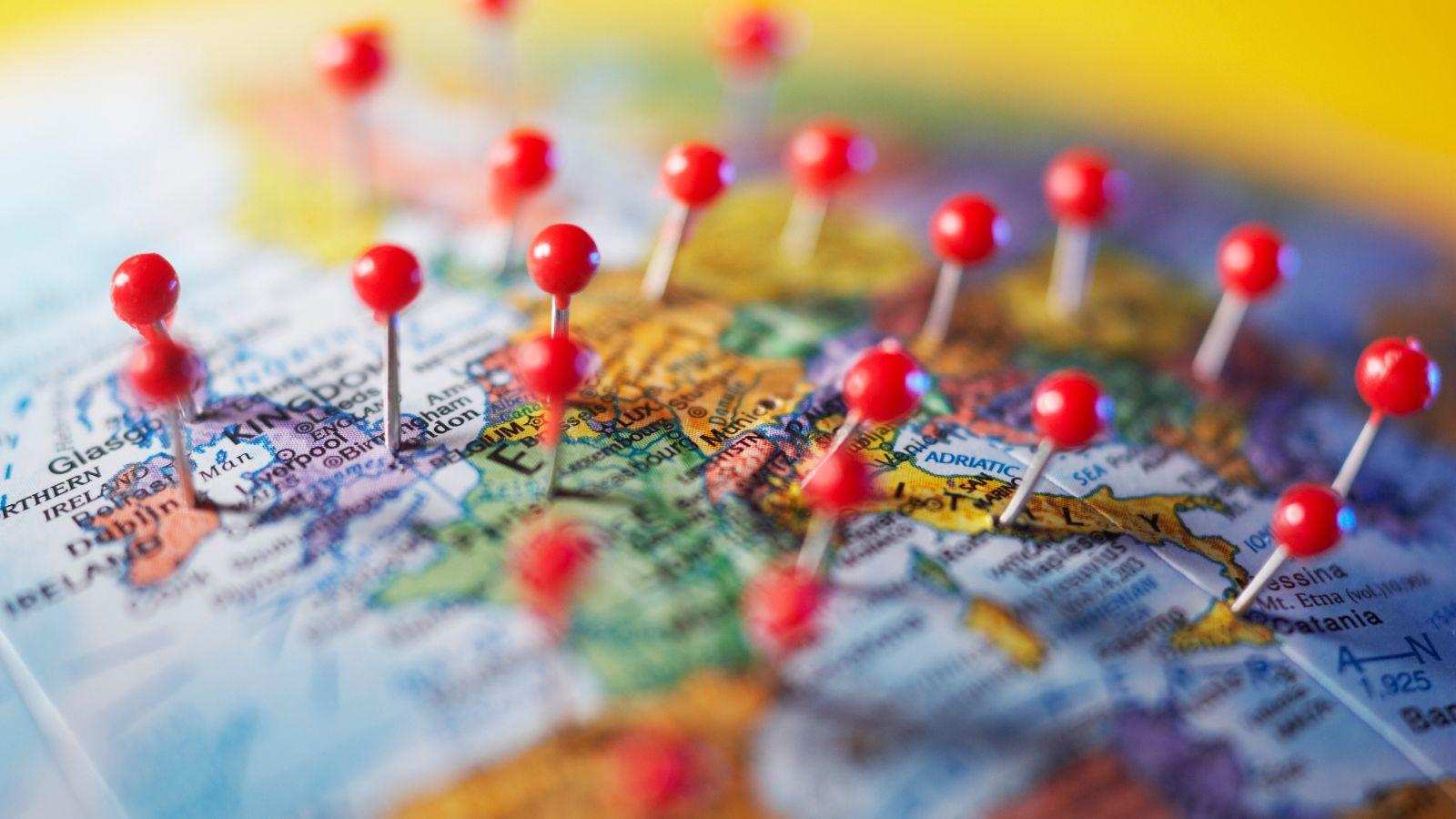 Nahaufnahme eines mit Nadeln gespickten Globus, Fokus auf Europa