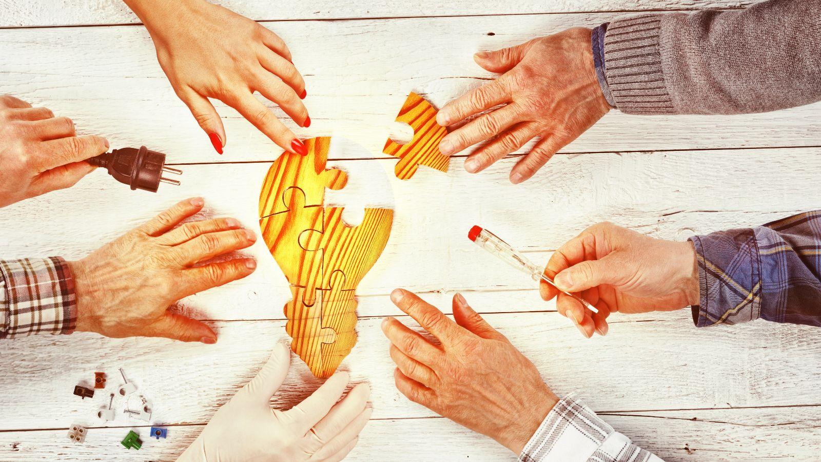 Sechs unterschiedliche Hände setzen gemeinsam ein Glühbirnen-Puzzle zusammen,  teilweise benutzen sie Hilfsmittel.