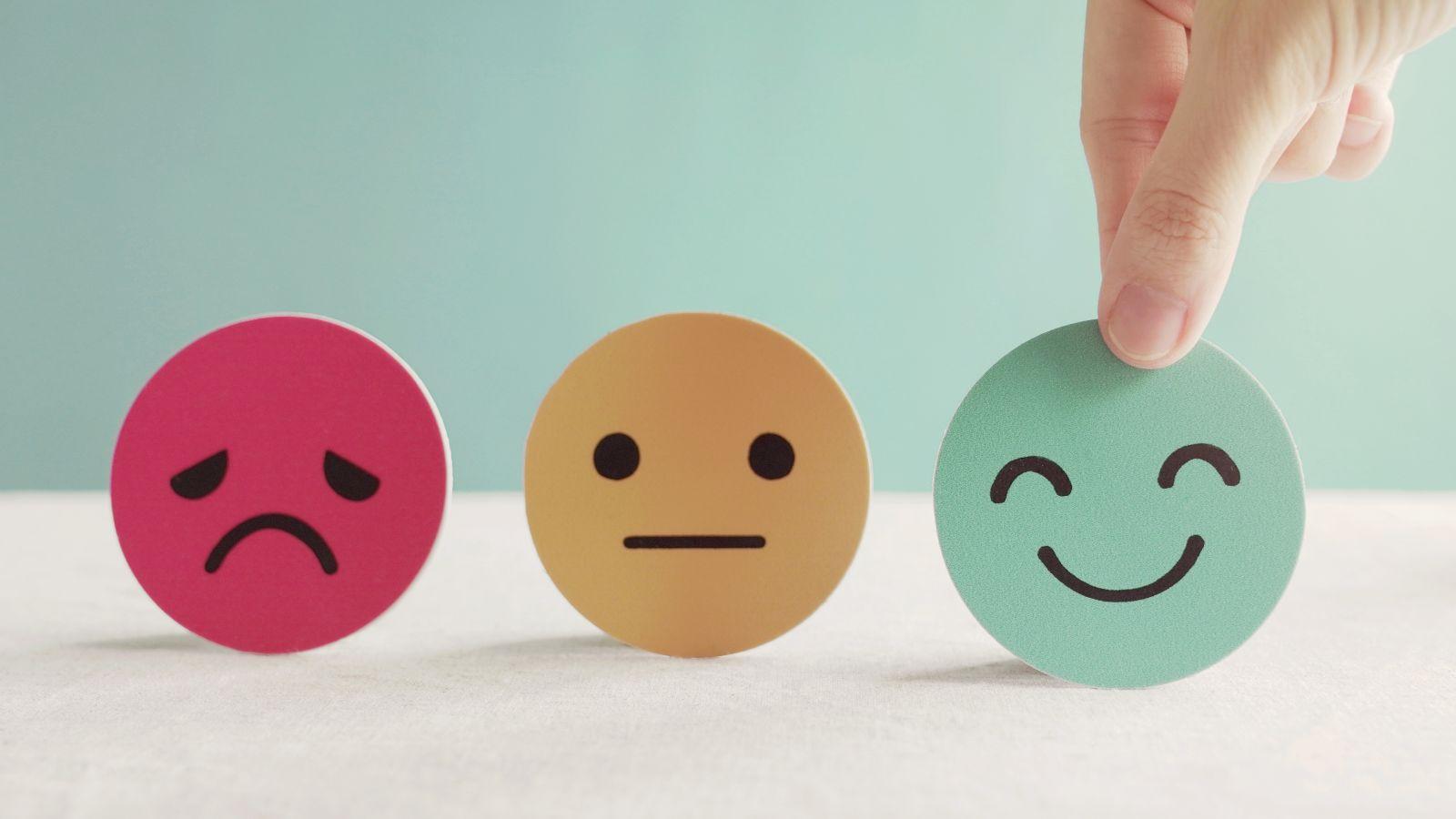 Drei plastische Smileys nebeneinander, von einem roten traurigen über ein neutrales gelbes bis hin zu einem grünen vergnügten, das von einer Hand gehalten wird.