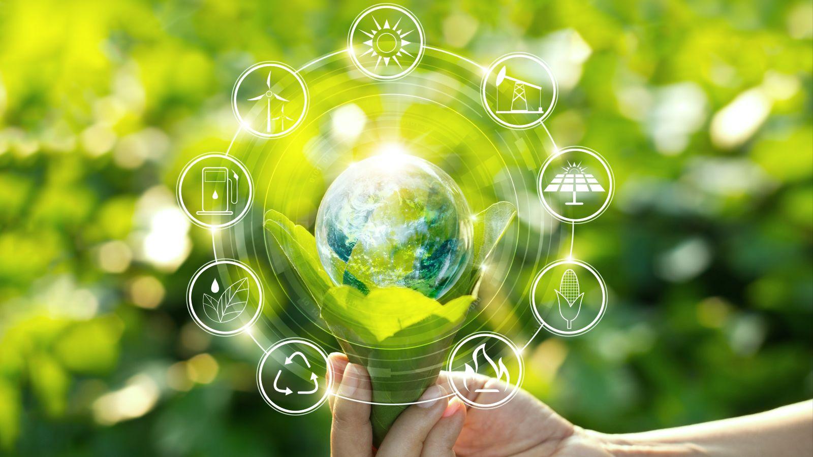 Leuchtende Erdkugel entspringt einer Pflanze, die von Hand gehalten gehalten und von technischen Symbolen umkreist wird, vor gr�nen Pflanzen im Hintergrund.