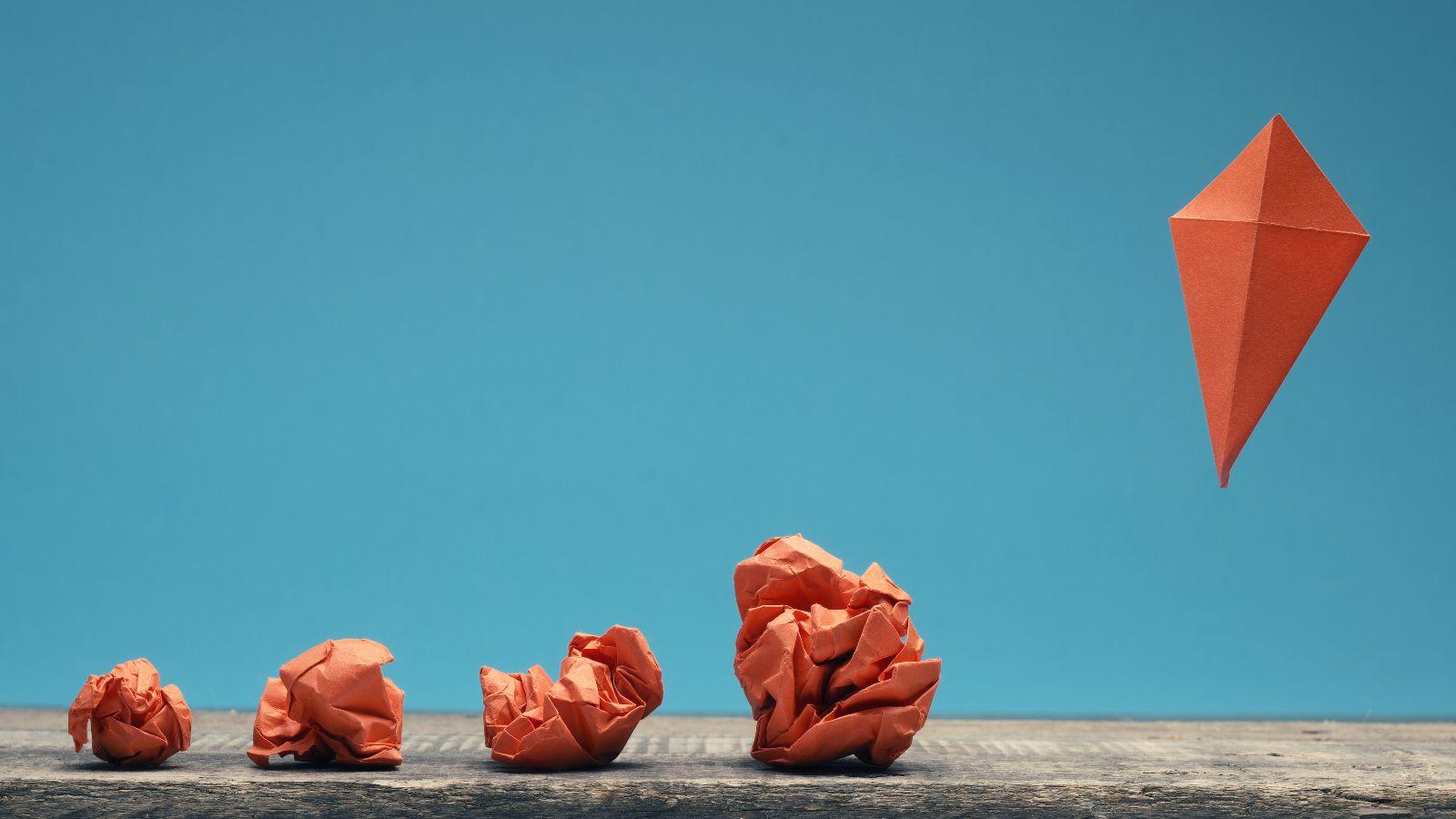 Vier orange zusammengeknüllte Papiere liegen nebeneinander, ein fünftes fliegt als gefalteter Drachen vor blauem Grund nach oben.