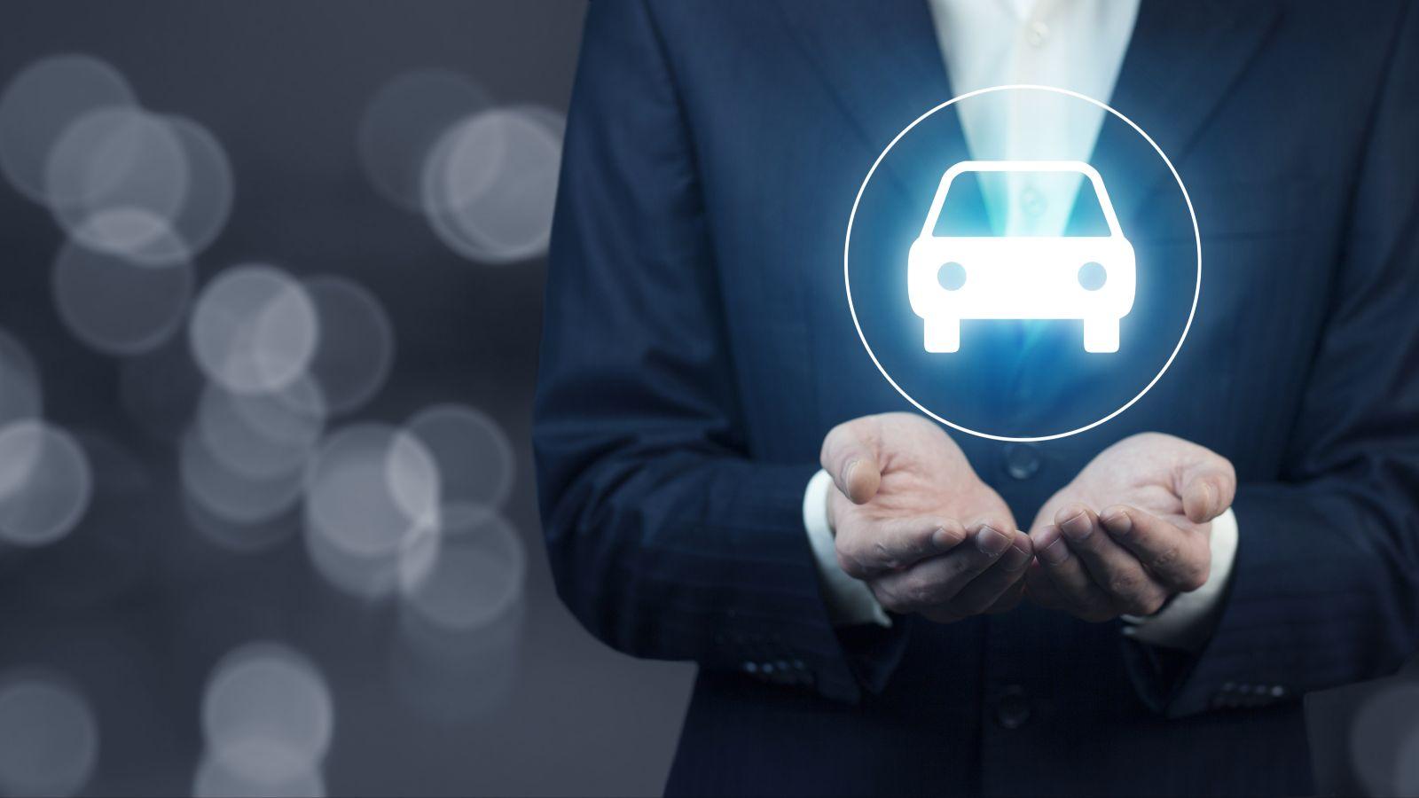 Leuchtendes Symbol eines Autos schwebt über den Handflächen einer formal gekleidete Person